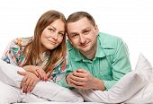 picture of laying-in-bed  - Happy smiling couple laying laughing in bed on white background - JPG