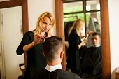 stock photo of beauty parlour  - Female hairdresser cutting hair of smiling man client at beauty parlour - JPG