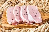 picture of shoulder-blade  - Boneless Pork Loin Steaks on cutting board and straw - JPG