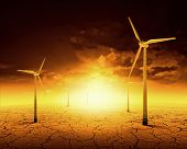stock photo of windmills  - Concept of alternative electricity power with windmills on sunset background - JPG