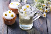 stock photo of chamomile  - Cup of chamomile tea with chamomile flowers and tasty muffins on color wooden background - JPG