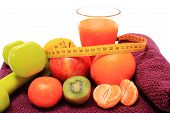 foto of immune  - Fresh fruits with tape measure glass of juice and green dumbbells for fitness lying on purple towel concept for slimming healthy nutrition and strengthening immunity - JPG