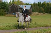 picture of appaloosa  - A man in tuxedo riding appaloosa mare with western tack - JPG