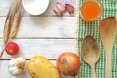 stock photo of ingredient  - Some recipe ingredients on a white wooden table decorated with a green tablecloth.  Ingredients conforming a frame. Empty space for the editor