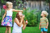 picture of blowers  - mother and her children play with bubble blower on green lawn - JPG