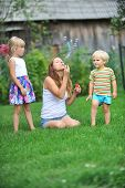 image of blowers  - mother and her children play with bubble blower on green lawn - JPG