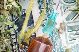 foto of seed bearing  - Syringe with brown liquid and hemp seeds and dried hemp leaves on dollar banknotes - JPG