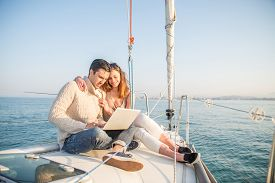 stock photo of boat  - Couple sitting on a sailing boat looking at laptop computer  - JPG