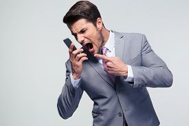 picture of shout  - Angry businessman shouting on the phone over gray background - JPG