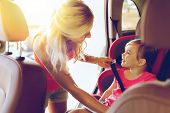 family, transport, safety, road trip and people concept - happy mother fastening child with car seat poster
