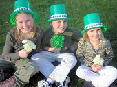 stock photo of saint patricks day  - three children dressed up in green offer a st patricks day greeting complete with flowers - JPG