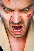 Portrait of sinister man wolf with scary green artificial eyes, mouth open