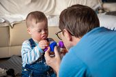 Cute Baby Boy With Down Syndrome Playing With Dad On In Home Living Room poster
