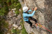 Climber In Helmet Overcomes Rocky Wall With A Rope Insurance poster
