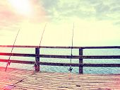 Abstract Effect.  Several Fishing Rods Against The Wooden Railing Of The Beach Pier. Overcast Day, W poster
