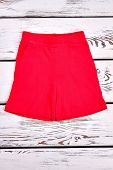 Brightful Brand Shorts For Kids. Red Color Beautiful Cotton Shorts For Childrens, White Wooden Backg poster