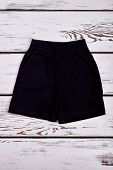 Black Casual Shorts For Baby Boy. Top View Of Boys Summer Shorts On White Wooden Background. Childre poster