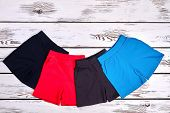 Set Of Kids Colored Cotton Shorts. Collection Of New Brand Shorts For Childrens On White Wooden Back poster