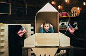 Boy Play With Rocket, Cosmonaut Sit In Usa Rocket Made Out Of Cardboard Box. Kid Excited Sit In Card poster