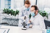 Scientific Researchers In White Coats And Medical Masks Working Together In Lab poster