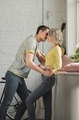 Affectionate Couple Kissing Near Windowsill At Home poster