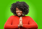 Beautiful african woman with hands together in praying gesture, expressing hope and please concept poster