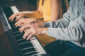 Piano players playing together four-handed piece during music school rehearsal  poster