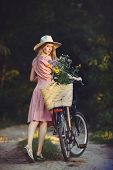 Beautiful Girl Wearing A Nice Pink Dress Having Fun In A Park With A Bicycle Holding A Beautiful Bas poster