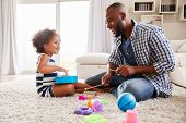 Young black father playing with daughter in the sitting room poster