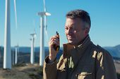 Man talking with portable radio transmitter outdoor over the wind turbines, image toned. Windmill ge poster