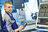 industrial worker operating cnc milling machine in metal machining industry poster