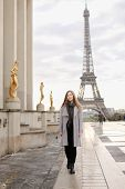 Young Woman In Grey Coat Standing On Trocadero Square Near Gilded Statues And Eiffel Tower In Paris. poster