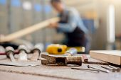 Equipment On Wooden Desk With Man Working In Workshop Background. poster