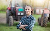 Young Pretty Farmer Woman Standing On Farmland With Crossed Arms And Tractors In Background poster