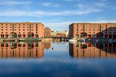 View Across The Albert Dock In Liverpool Towards A Bridge. The Buildings, The Bridge And The Boats A poster
