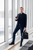 Business Man Using Mobile Phone App In Airport. Young Business Professional Man Texting Smartphone W poster