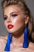 Young Blond Girl With Bright Makeup, Perfect Skin, Volume Hairdo And Bright Red Lipstick. Blue Earri poster