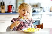 Lovely Toddler Girl Eating Healthy Fried Potatoes For Lunch. Cute Happy Baby Child In Colorful Cloth poster