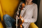 Beautiful Young Woman Musician Posing With A Violin In A Soft Chair. Violinist Woman Holds Her Instr poster