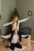 Happy Husband And Wife At The Christmas Tree At Home. Wife On Husband S Back. poster