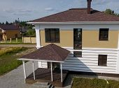 House With A Roof From A Bituminous Tile. New Brick House. Bituminous Tile For A Roof. A Roof From A poster