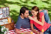 Постер, плакат: Женщина положить пищи в рот друзей как они лежат на одеяло с пикник корзины еда и Фло