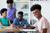 Young African American Male Student Learning At Desk At School With Teacher And Group Of Students At poster