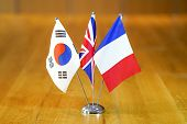 Three Flags On The Table. Flags Of South Korea, United Kingdom And France. Flags Of South Korea, Fra poster