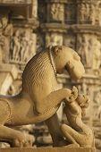 stock photo of kandariya mahadeva temple  - Sculptures of a mythical lion and woman at the Kandariya Mahadeva Hindu Temple at Khajuraho Uttar Pradesh India - JPG