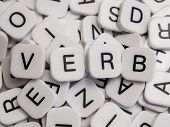 image of verbs  - Verb letters spelled on white letter tiles - JPG