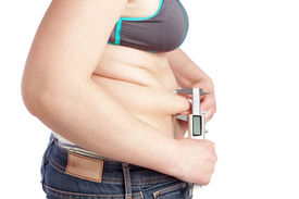 pic of pot-bellied  - Fat woman measuring calipers layer of fat belly - JPG
