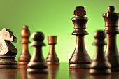 picture of chess pieces  - Playing a game of chess with selective focus between chess pieces on a chess board to a king in dark wood against a green background - JPG