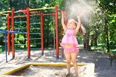 A little girl cheerfully throws up sand in the sandbox