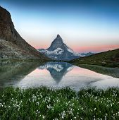 Matterhorn reflection in Riffelsee with flowers, Zermatt, Alps, Switzerland